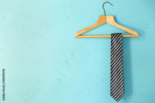 Tela Male tie hanging on the rack, blue background