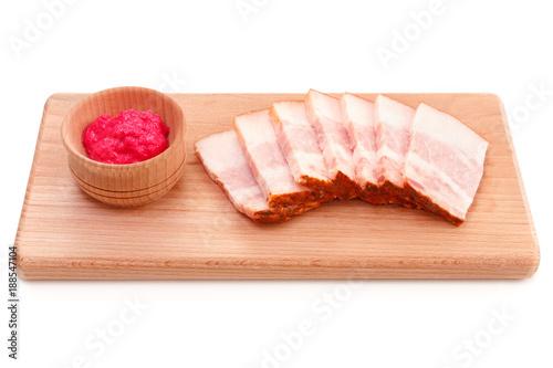 Jowl pork bacon sliced on wooden plate with red horseradish sauce Fototapeta