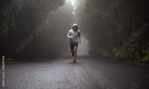 Portrait of a young athlete running on the road