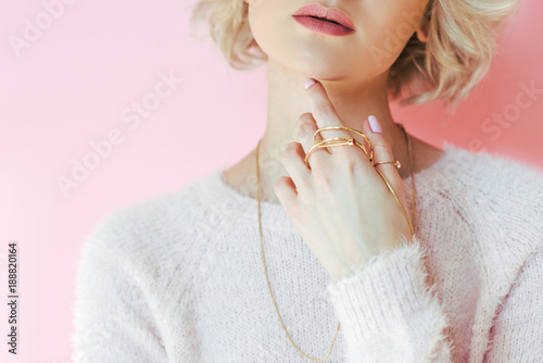 Vászonkép cropped shot of sensual young woman holding jewelry in hand isolated on pink