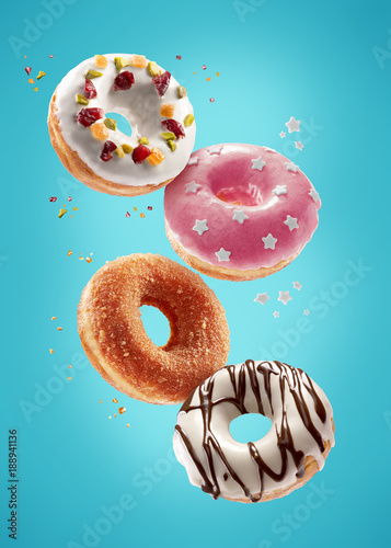 Donuts selection flying on blue background. Various doughnuts isolated on colorful background