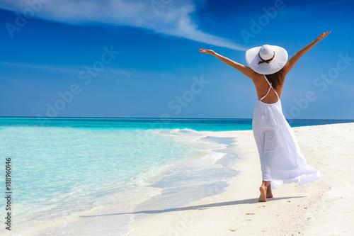 Obraz na płótnie Attraktive Frau in weißem Kleid läuft an einem tropischen Strand und ist glückli