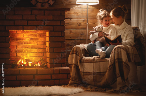 Fotografia happy family mother and child daughter read book on winter evening near fireplac