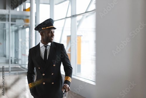 Fotografija handsome young pilot with luggage at airport looking away