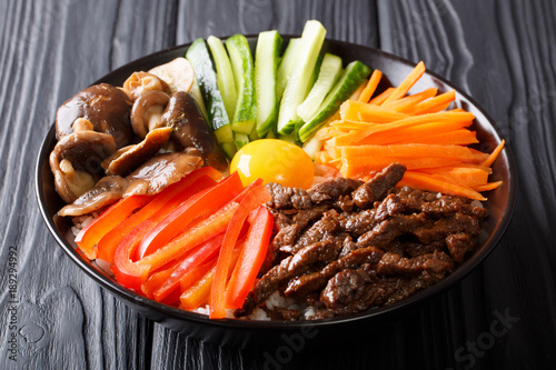 Korean healthy food Bibimbap of rice with fried beef, raw egg, vegetables, shiitake close-up in a bowl on the table. horizontal