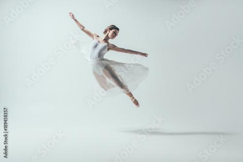 Valokuvatapetti elegant ballet dancer in white dress jumping in studio, isolated on white