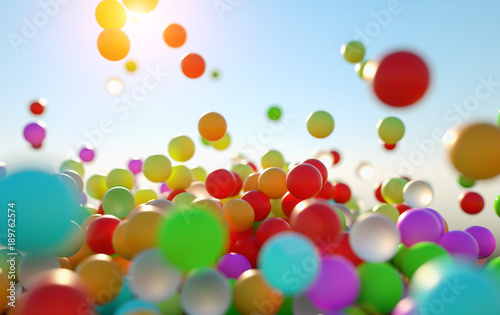 Valokuva colorful bouncing balls outdoors against blue sunny sky