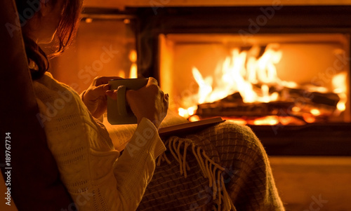 Fotografia Young woman  sitting at home by the fireplace and reading a book.