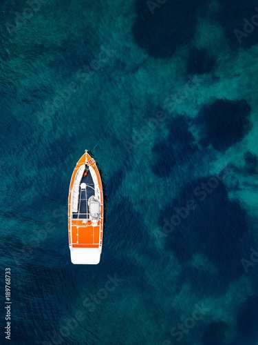 Red boat in deep blue water. Aerial view