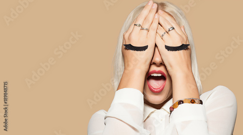 Fotografia Funny young woman with eyelashes painted on the hand