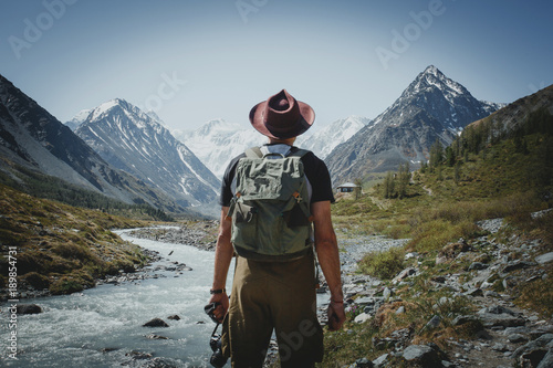 Tableau sur Toile A traveler with a backpack stands with his back against the backdrop of the moun