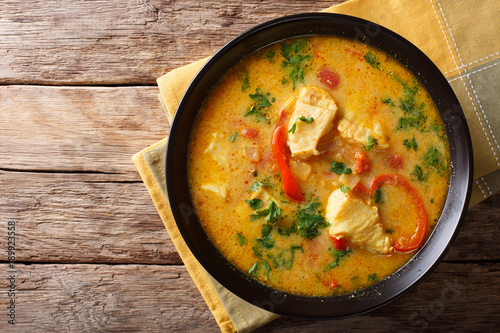 Brazilian food: Moqueca Baiana of fish and bell peppers in spicy coconut sauce close-up on a plate. horizontal top view