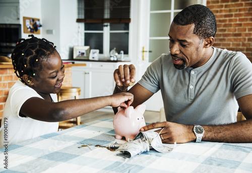 Fotomural Dad and daughter saving money to piggy bank