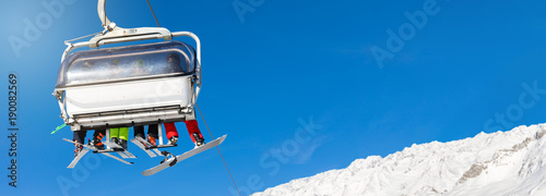 Canvas Print skiers and snowboarders in a ski lift against clear blue sky