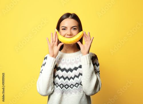 Funny portrait of young woman with banana on color background