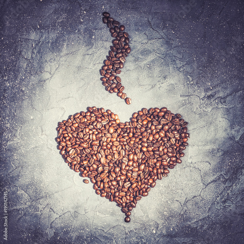 Heart shape from roasted coffee beans with steam on a violet stone background vintage rustic toned food concept background macro close-up
