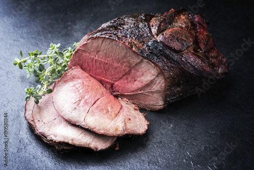 Barbecue dry aged haunch of venison with herbs as close-up on a board Fototapeta