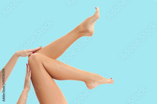 Fotografia Woman's legs with smooth skin after depilation on pastel background