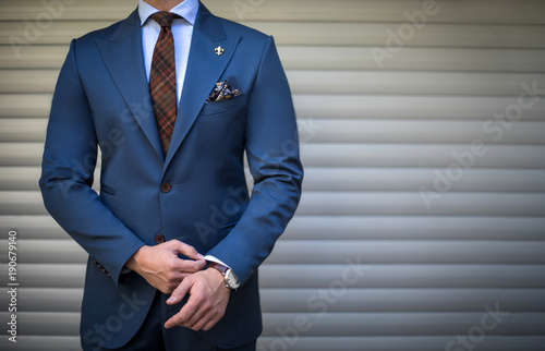 Valokuva Male model in tailored suit posing outdoors and fixing his cufflinks
