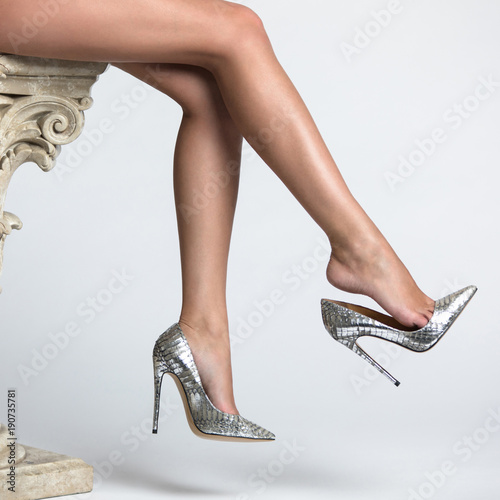 Fotografia Beautiful women legs in high heel shoes on a white background.