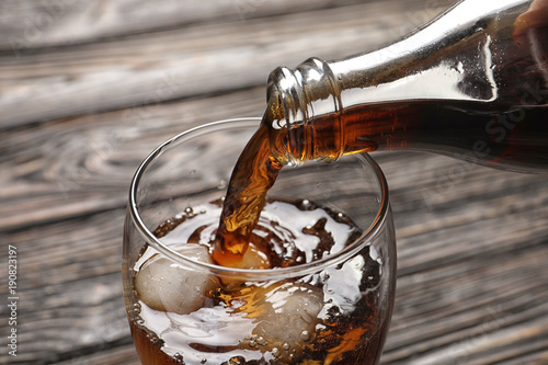 Pouring cola from bottle into glass with ice on wooden background, closeup