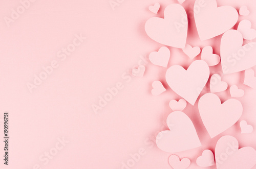 Paper pink hearts fly on soft pink color background, border, copy space. Valentine day concept for design.