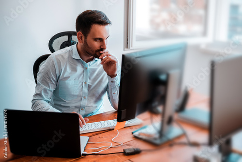 Foto Concentrated businessman analyzing graphs in his office at computer