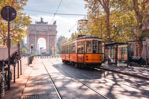 Fototapeta premium Słynny zabytkowy tramwaj w centrum Starego Miasta w Mediolanie w słoneczny dzień, Lombardia, Włochy. Łuk Pokoju, czyli Arco della Pace w tle.