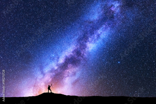 Fotografie, Obraz Silhouette of happy woman with trekking poles against purple Milky Way at night