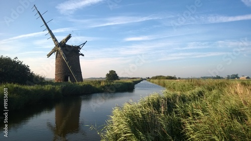 Canvas Print Ancient brick windmill with wood sails reflected in the river water of the Norfo