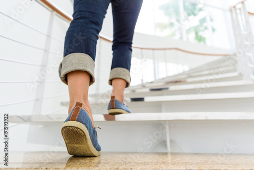 Slika na platnu Young adult woman walking up the stairs with sun sport background