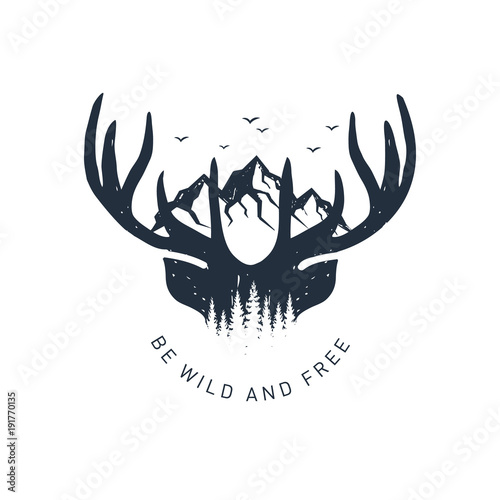 Tela Hand drawn travel badge with deer antlers and mountains textured vector illustration and Be wild and free inspirational lettering