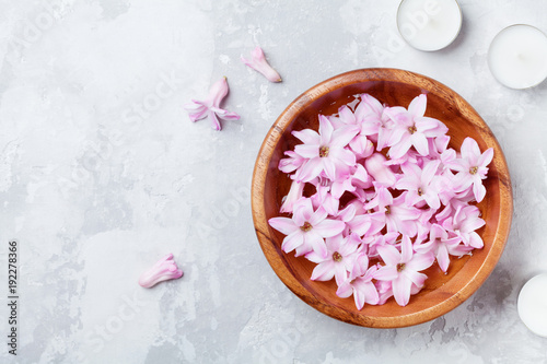 Beauty, spa and wellness composition of perfumed pink flowers water in wooden bowl and candles on stone table. Aromatherapy background. Top view, flat lay style.
