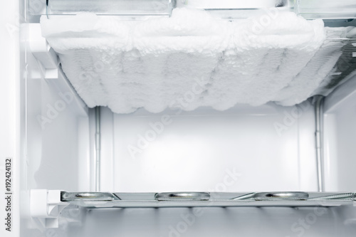 Frozen ice in the empty freezer. Problem and solution concept.