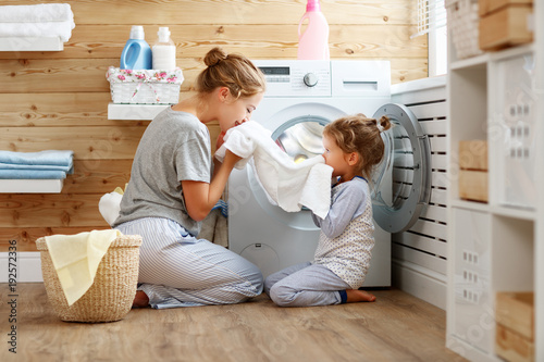 Fototapeta Happy family mother housewife and child   in laundry with washing machine