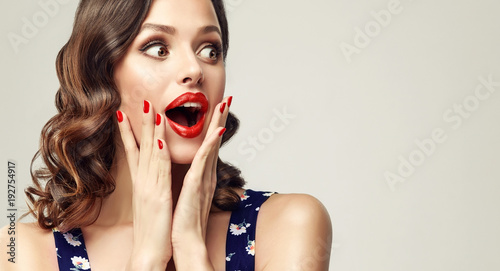 Photo Surprised and amazed girl holds  her cheeks and looks in the side