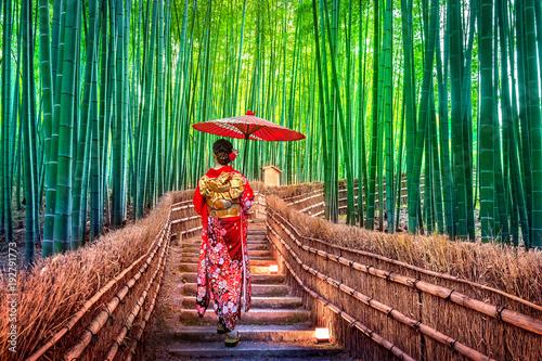 Fototapeta premium Bambusowy Las. Azjatycka kobieta jest ubranym japońskiego tradycyjnego kimono przy Bambusowym lasem w Kyoto, Japonia.