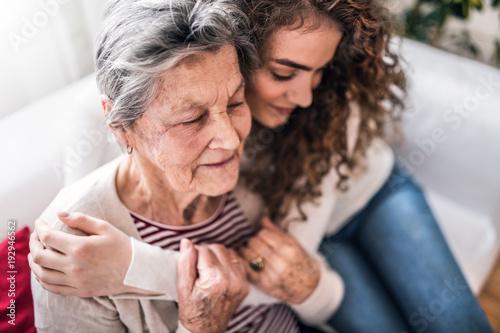 Fototapeta A teenage girl with grandmother at home, hugging.