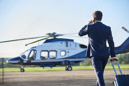 Valokuvatapetti Rear View Of Businessman Walking Towards Helicopter Whilst Talking On Mobile Pho