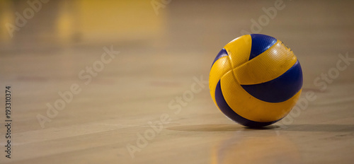 Volleyball ball on blurred wooden parquet background. Banner, space for text, close up view with details.