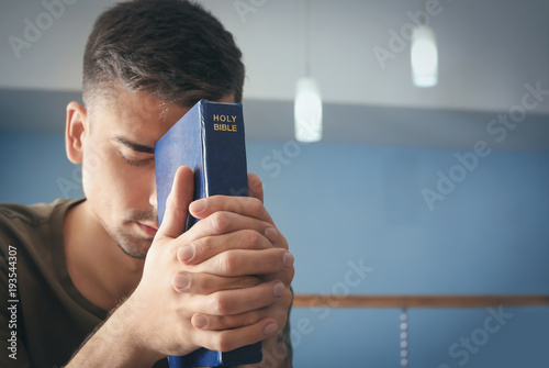 Fototapeta Religious young man with Bible praying at home