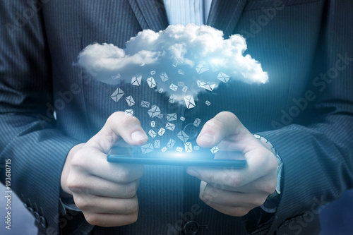 Businessman running with email in the cloud.