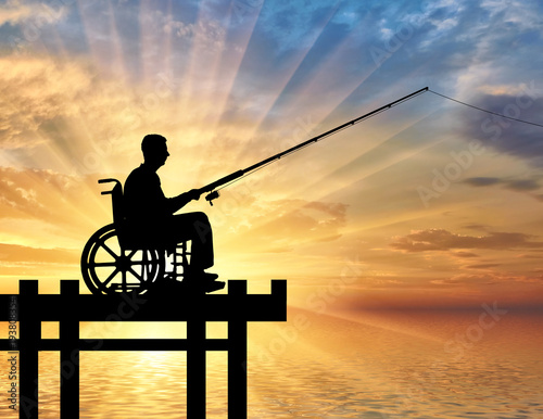 Silhouette of a disabled man in a wheelchair with a fishing rod in his hand fish Fotobehang