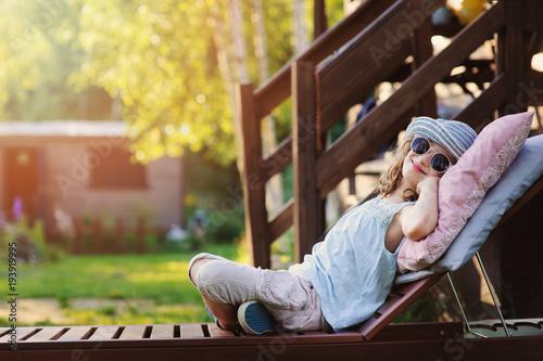 Fotografia, Obraz summer portrait of happy kid girl relaxing on lounger in garden on vacation