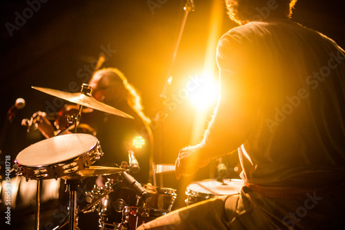 Fotografia Drummer on stage playing with a band with gold yellow light shining in backgroun