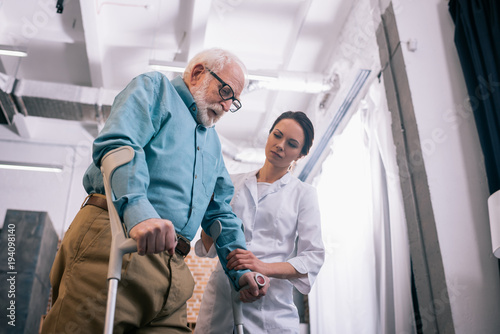 Fotografia Doctor supporting male patient with crutches