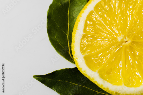 cut lemon with green leaves