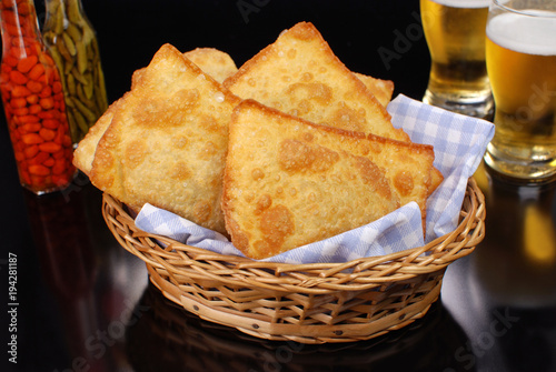 Brazilian typical pastry called pastel in black pub table background