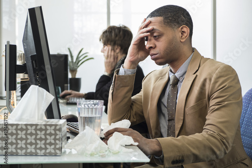 Carta da parati Business man working at his desk sick with a cold and fever