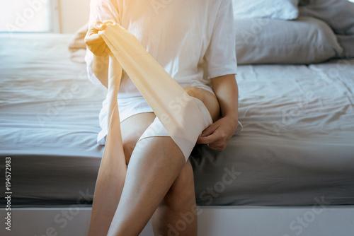 Billede på lærred Woman using elastic bandage with leg,Female putting bandage on his injured knee